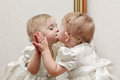 Cute baby kissing mirror oneself reflection Stock Images