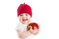 Cute baby in a knitted apple hat biting in a red ripe apple isolated on white little Stock Photos