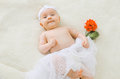 Cute baby lying on a bed with flower Royalty Free Stock Photo
