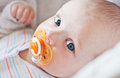 Cute baby with pacifier lying in a cradle on white background Stock Photo