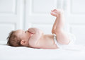 Cute baby playing with its legs and sucking on its hand Royalty Free Stock Photo