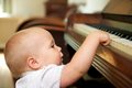 Cute baby playing on piano portrait of a Royalty Free Stock Image
