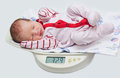 Cute baby on the scales Royalty Free Stock Photo