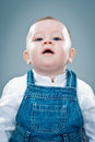Cute baby with serious expression over grey background Royalty Free Stock Images