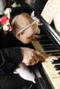 Cute baby sits at knees of father and plays piano her in room focus on hands Royalty Free Stock Images