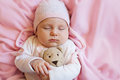 Cute baby sleeping with teddy bear toy on pink soft bed at home