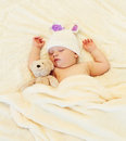 Cute baby sleeping with teddy bear on white bed home