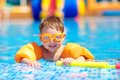Cute baby swimming in pool with inflatable arm rings boy Stock Photography
