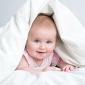Cute baby under a blanket white in bed Stock Photos