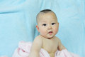 Cute baby whith pink towel sits wrapped in bath after bathing Royalty Free Stock Image