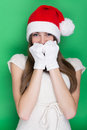 Cute bashful teenage girl with santa hat pretty caucasian beanie and white soft gloves looking at camera against green background Stock Photography