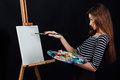 Cute beautiful girl artist painting a picture on canvas an easel. Space for text. Studio black background. Royalty Free Stock Photo