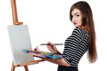 Cute beautiful girl artist painting a picture on  canvas  easel. Space for text. Studio white background, isolated. Royalty Free Stock Photo