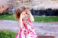 Cute beautiful little girl hides her face in her hands Stock Images