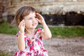 Cute beautiful little girl hides her face in her hands Royalty Free Stock Photography