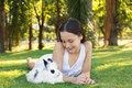 Cute beautiful smiling teen girl looking at white black rabbit on grass and baby selective focus on Royalty Free Stock Image