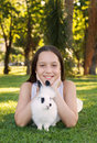 Cute beautiful smiling teen girl with white black baby rabbit on grass and selective focuson s face Stock Photo