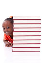 Cute black african american little girl hidden behind a stack of books isolated on white background people children Stock Images