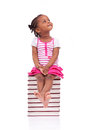 Cute black african american little girl seated in a stack of boo books isolated on white background people children Stock Image