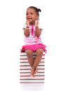 Cute black african american little girl seated in a stack of boo books isolated on white background people children Royalty Free Stock Photos