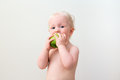 Cute blond baby eating apple closeup portrait of a with blue eyes on a light background Royalty Free Stock Photography
