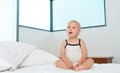 image photo : Cute blond baby sitting on bed alone