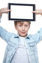 Cute blond boy in a blue shirt holding a tablet pc with white screen showing brown above his head isolated on background Royalty Free Stock Photo