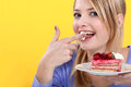 Cute blond eating a cake. Stock Image