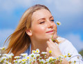 Cute blond female lying down on floral field and enjoying smell of little white daisy flower summer season vacation and resting Stock Image