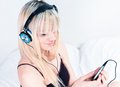 Cute blond girl listening to music on her smartphone Royalty Free Stock Image