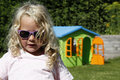Cute blond girl with playhouse child sunglasses in purple little hearts wendy house or cubby house in the bachground of the garden Royalty Free Stock Photography