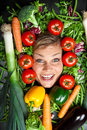 Cute blond girl shot in studio with vegetables aroound the head Royalty Free Stock Photo