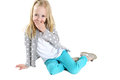 Cute blond girl sitting hand to mouth laughing Royalty Free Stock Photo