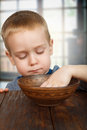 Cute blonde boy eats with hands small child sitting at wooden table hand Stock Photo
