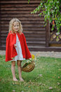 Cute blonde child girl playing little red riding hood in summer garden cape holding basket with flowers Royalty Free Stock Photography