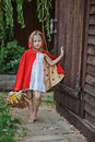 Cute blonde child girl playing little red riding hood in summer garden Royalty Free Stock Photo