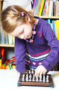Cute, blonde girl playing chess Royalty Free Stock Photo