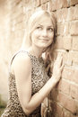 Cute  blonde lady standing near a brick wall Stock Photo