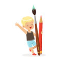 Cute blonde little boy holding giant red pencil and paintbrush cartoon vector Illustration Royalty Free Stock Photo
