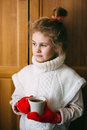 Cute blonde little girl holding hot steaming tea cup close up photo Royalty Free Stock Photo
