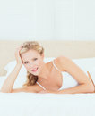 Cute blonde lying on her bed smiling at camera home in the bedroom Royalty Free Stock Images