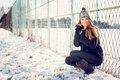 Cute blonde teenage girl outdoors in park in winter happy caucasian posing young woman with snow casual Royalty Free Stock Image