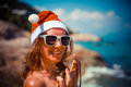 Cute blonde woman in bikini, sunglasses and santa hat on at exotic tropical beach. Holiday concept for New Years Cards. Royalty Free Stock Photo