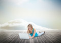 Cute blonde woman laying and using laptop over wooden boards leading out to the horizon Stock Photo