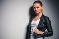 Cute blonde woman in leather jacket holds her collar Royalty Free Stock Photo