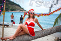 Cute blonde woman in red dress, sunglasses and santa hat sitting on palm tree at exotic tropical beach. Holiday concept Royalty Free Stock Photo