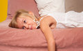 Cute bored little girl lying on the bed Royalty Free Stock Photos
