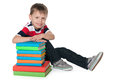 Cute boy with books a smiling is sitting on the floor near the pile of against the white background Stock Photo