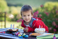 Cute boy celebrating his fifth birthday outdoor with a cake and presents Stock Photography