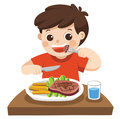 A cute boy is eating steak with vegetables.